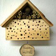 Kleines Holzhäuschen mit Lächern und Stroh
