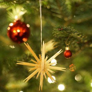 Weihnachtsbaum mit Holzstern und roten Kugeln