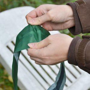 Grünes Band wird von zwei Händen auseinander gezogen