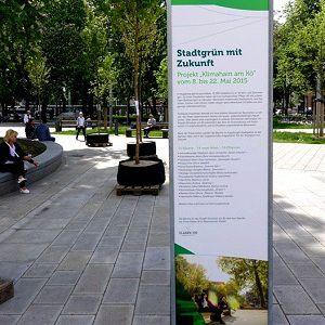 """Tafel mit Aufschrift """"Stadtgrün mit Zukunft"""" in einem Park"""