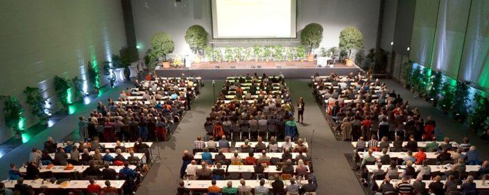 Großer Saal mit Bühne und sitzenden Gästen der Baumpflegetage