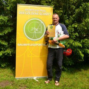 Preisträger Jürgen Unger vor dem Logo des Baumpflegeportals