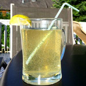 Glas mit gelber spritziger Flüssigkeit