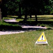 """In einem Park steht ein Schild mit der Aufschrift """"Baumarbeiten"""""""