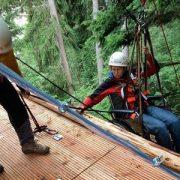 Auch Frau im Rollstuhl wird an Kletterseilen auf eine Holzplattform gezogen
