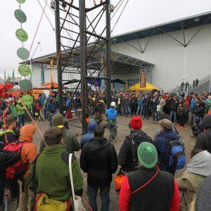 Kletterturm vor einer Messehalle mit zahlreichen Zusachauern