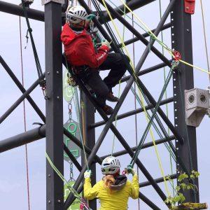 Zwei Personen klettern an einem Stahlgerüst