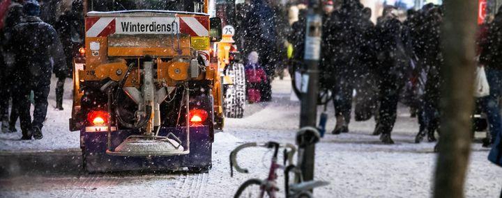 Winterfahrzeug streut in der Stadt einen Fußweg