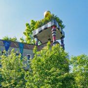 Ein Haus von Hundertwasser mit Bäumen auf dem Dach
