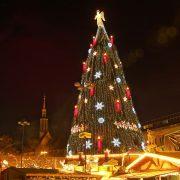 Weihnachtsbaum mit riesiegen Kerzen zwischen Weihnachtsmarktbuden