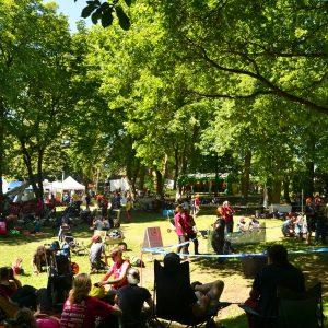 In einem Park sitzen Menschen auf decken und Stühlen.