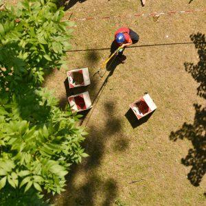 Eine Frau schießt mit einer großen Zwille ein Schnurr in den Baum