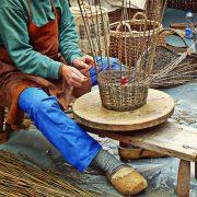 Ein Mann felchtet aus Weidenruten einen Korb.