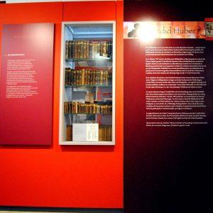 Ausstellungsvitrine mit Holzbüchern im Zentrum