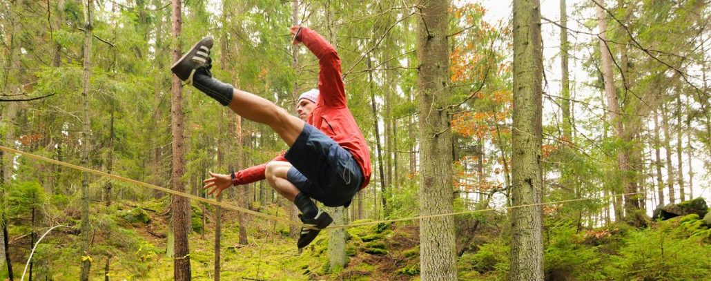 Eine Person balanciert auf einer Slackline im Wald