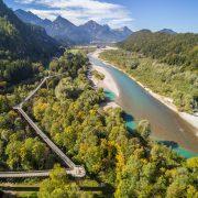 Neben einen Fluß und vor einem Bergpanorama geht ein Weg durch Baumkronen