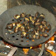 Geröstete Esskastanien in einer Eisenpfanne über Feuer