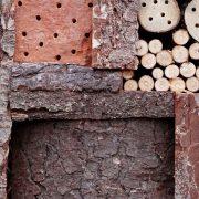 Insektenhotel mit Ton, Holz und Rinden-Füllung.